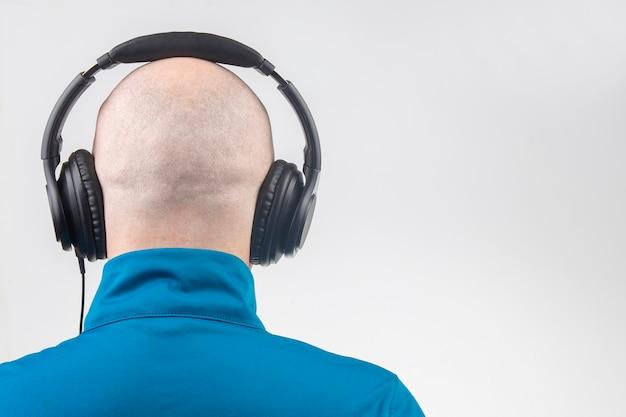 Achterkant van het hoofd van een kale man met koptelefoon op witte achtergrond