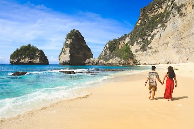 Achterkant van het paar lopen op diamond strand in nusa penida eiland, bali in indonesië.