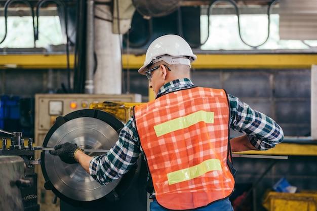 Achterkant van ingenieur-voorman of fabrieksarbeider die met draaibankmachine werkt