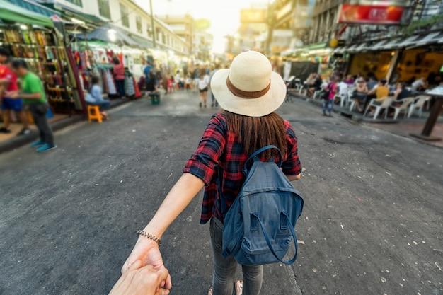 Achterkant van jonge aziatische reizende vrouwen die leiden