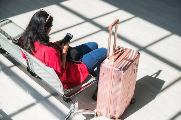Achterkant van jonge aziatische toerist zit op de wachtbank van de luchthaventerminal en gebruikt de telefoon om te chatten, sociale media te spelen terwijl ze op vertrek wachten. vakantieganger van reisvakantie.