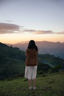 Achterkant van jonge aziatische vrouw die de wapens kruist met alleen gevoel op heuvel in de winter in nationaal park