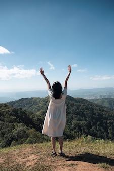 Achterkant van jonge aziatische vrouw die zich met het opheffen van handen bovenop heuvel bevindt