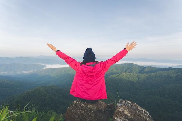 Achterkant van jonge vrouw zittend op een rots en zie uitzicht op de bovenste berg
