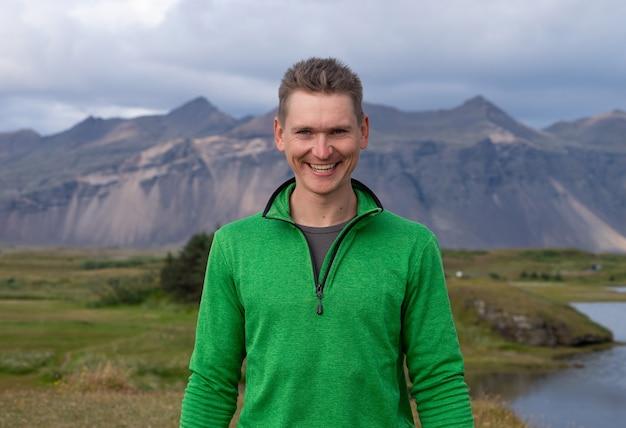 Achterkant van lange blanke man met groene jas staande over berg en mist achtergrond