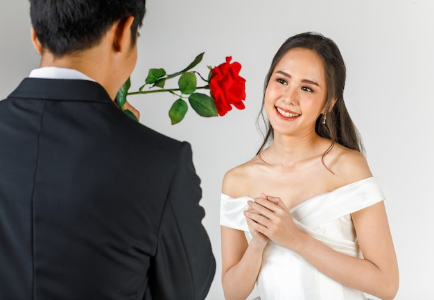 Achterkant van man met zwarte smoking die roos geeft aan jonge aantrekkelijke aziatische vrouw, binnenkort bruid en bruidegom, vrouw die witte trouwjurk draagt. concept voor pre-huwelijksfotografie.