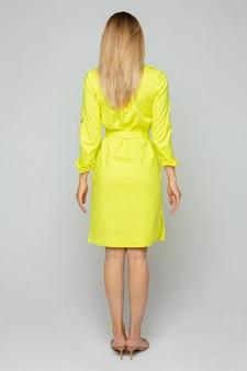 Achterkant van mooie jonge vrouw vormt voor de camera in gele jurk geïsoleerd op witte ruimte