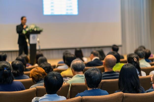 Achterkant van publiek luisteren de spreker met podium op het podium in de conferentie hal