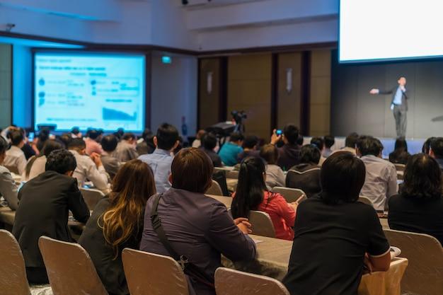 Achterkant van publiek zitten en luisteren naar de sprekers op het podium bij weinig licht