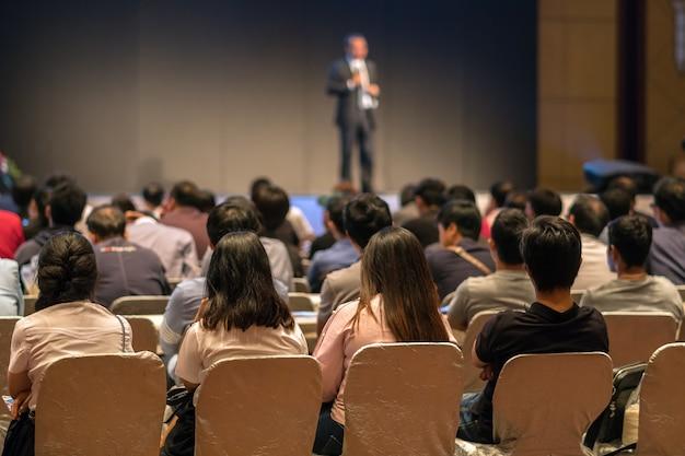 Achterkant van publiek zittend en luisterend naar de sprekers