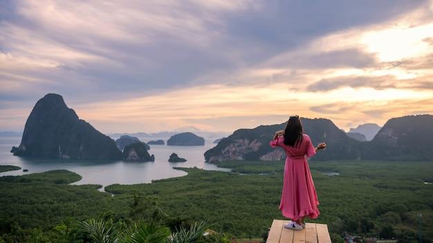 Achterkant van reizende vrouw op houten brug geniet van een prachtig uitzicht op de baai van phang nga bij zonsopgang