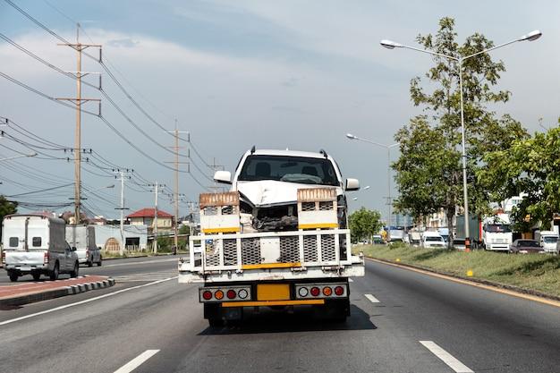 Achterkant van sleepwagen laden gebroken auto van crash ongeval op snelweg weg on