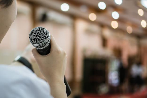 Achterkant van smart zakenvrouw spraak en spreken met microfoon