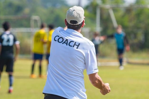 Achterkant van sportcoach die coach-overhemd draagt bij een openluchtsportgebied