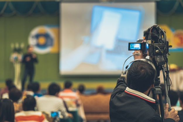 Achterkant van video cameraman die foto neemt naar aziatische spreker met casual pak