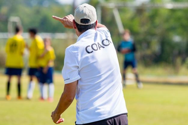 Achterkant van voetbaltrainer met wit coach-hemd die zijn team coacht tijdens een wedstrijd