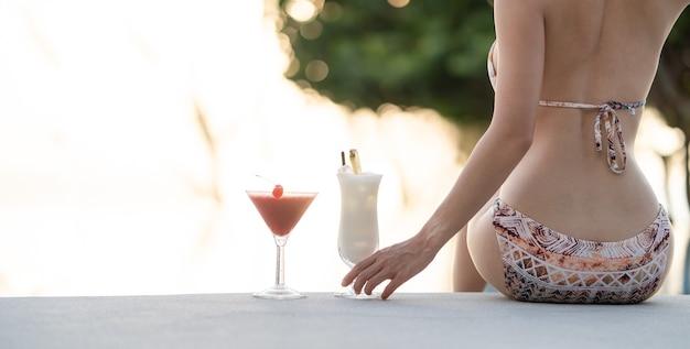 Achterkant van vrouw die bikini draagt zittend op de rand van zwembad drankje cocktail, vakantie zomervakantie.