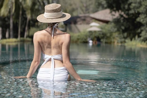Achterkant van vrouw die bikini en strohoed draagt die in pool ontspannen. spa-behandelingen concept.