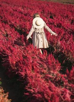 Achterkant van vrouw in trenchcoat en strooien hoed wandelen op het gebied van de rode bloem.