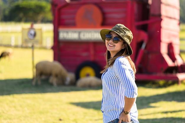 Achterkant van vrouwelijke boer werken en kijken op schapenboerderij