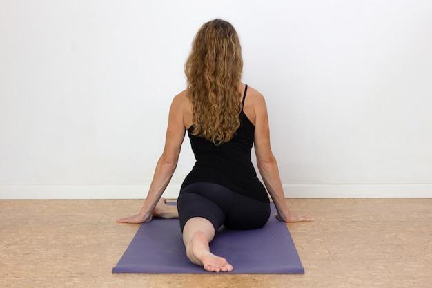 Achterkant van vrouwelijke yogi in zwaan pose op mat op witte achtergrond slanke vrouw doet yoga