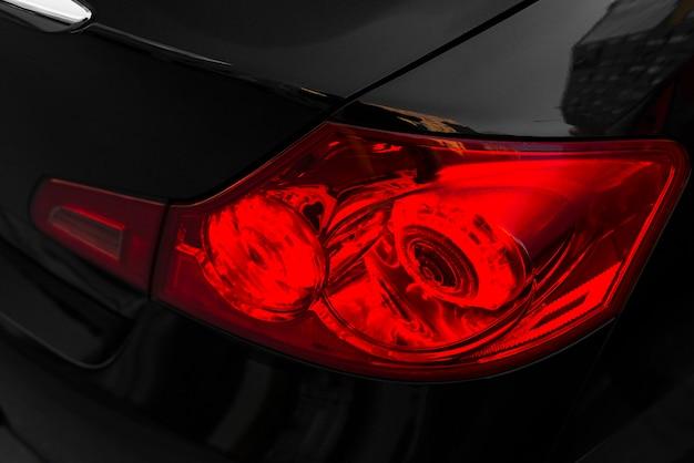 Achterkant van zwarte auto met rood achterlicht