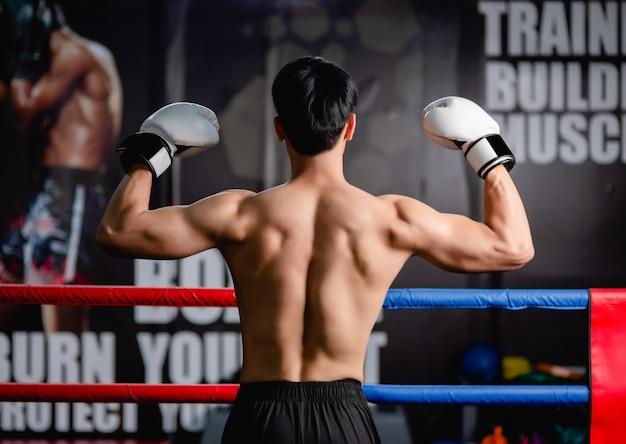 Achterlichaam van een jonge man zonder shirt in witte bokshandschoenen, staande pose, armen omhoog om de spier op zijn rug te laten zien op de boksring in de fitnessruimte,
