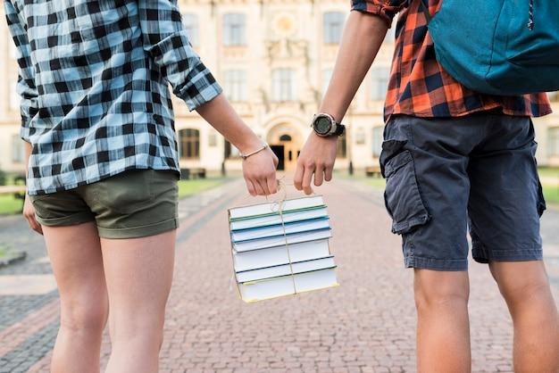 Achtermening dichte omhooggaande highschool studenten die boeken houden