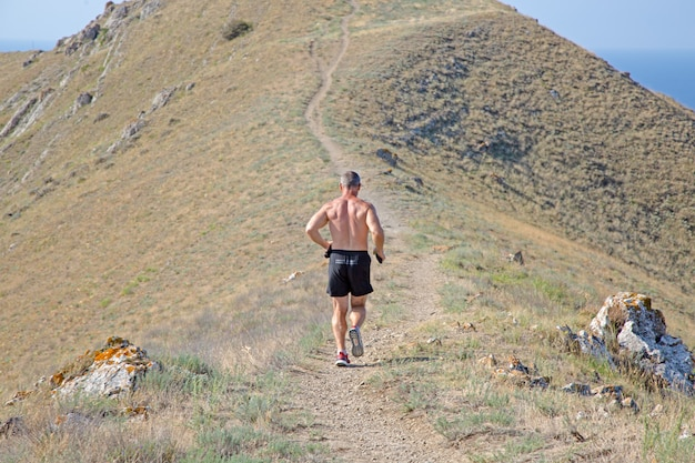 Achtermening die van atletische agent op een bergsleep lopen op een blauwe hemel