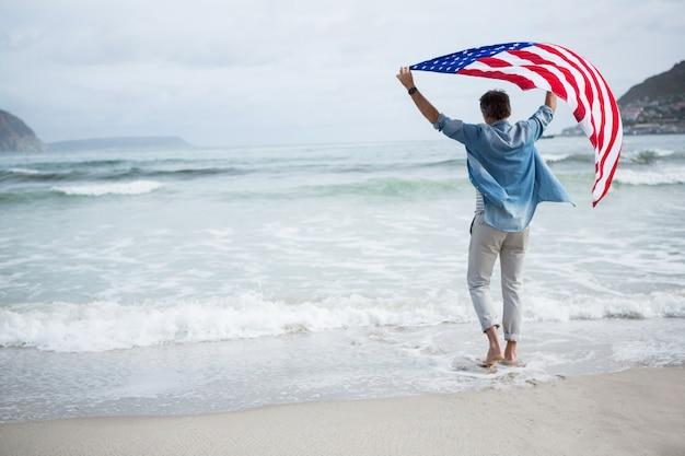 Achtermening die van de mens amerikaanse vlag op strand houden