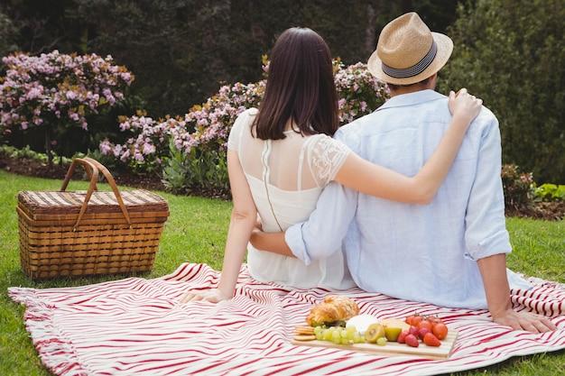 Achtermening die van jong paar elkaar in tuin omhelzen