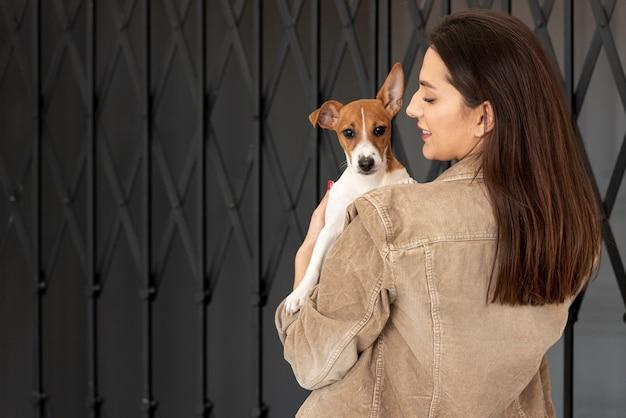 Achtermening die van vrouw haar hond buiten houden
