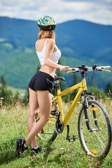 Achtermening die van vrouwelijke ruiter zich met gele bergfiets op een gras bevinden, die van de zomerdag in de bergen genieten. buitensportactiviteit, levensstijlconcept