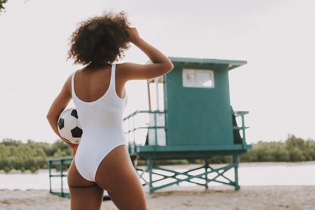 Achtermening over afrikaanse vrouw met voetbal.