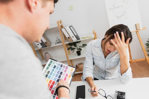 Achtermening uitgeputte vrouwenzitting bij haar bureau