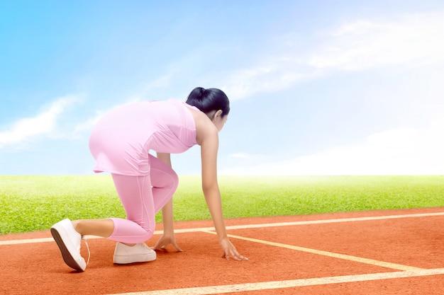 Achtermening van aziatische agentvrouw klaar om op de renbaan te lopen