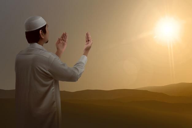 Achtermening van aziatische moslim opheffend hand en het bidden
