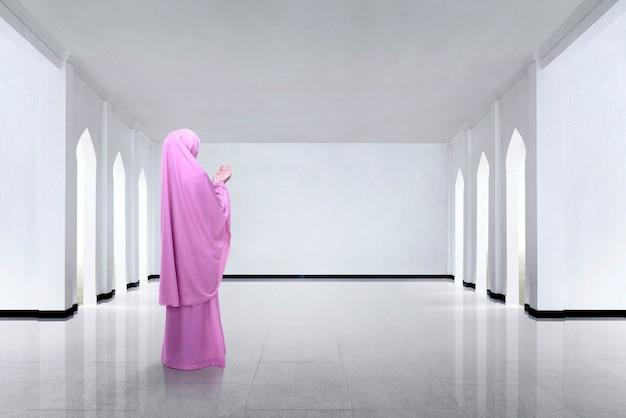 Achtermening van aziatische moslimvrouw die hand en het bidden opheffen