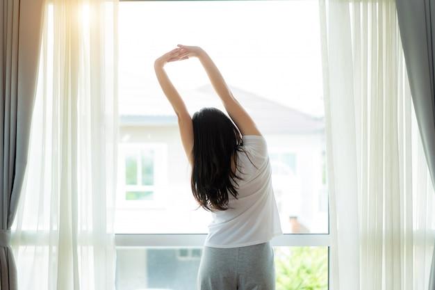 Achtermening van aziatische vrouw het uitrekken zich handen en lichaam dichtbij venster na kielzog omhoog in slaapkamer thuis. concept voor start nieuwe dag met geluk. het jonge gelukkige werkende vrouwelijke leven