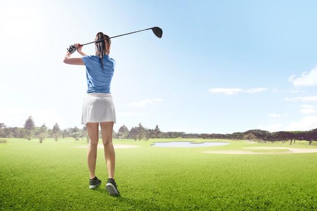 Achtermening van aziatische vrouw op lange aandrijvingsschommeling met houten club in de golfcursus met zandbunkers, vijver en bomen