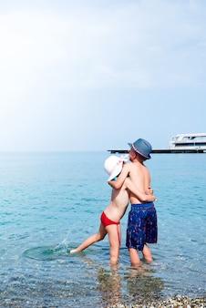 Achtermening van babygirl en babyboy het kussen op het strand in strohoeden bij de kust.