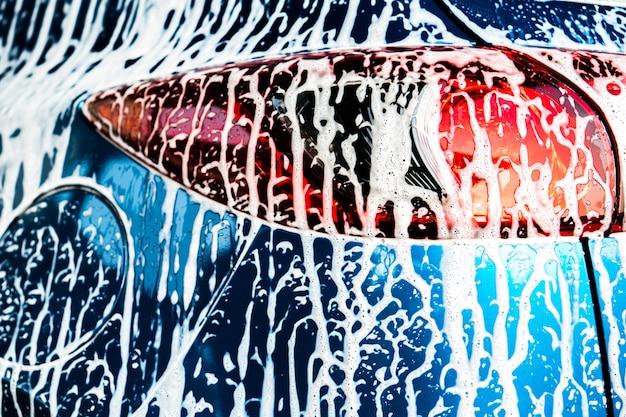 Achtermening van blauwe compacte suv-auto met sport en moderne ontwerpwas met zeep.