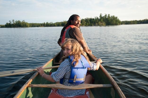 Achtermening van blond meisje en africian amerikaanse mens die in een kano bij meer van het hout, ontario roeien