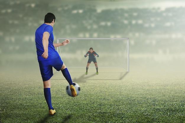 Achtermening van de aziatische voetbalstermensmens in actie
