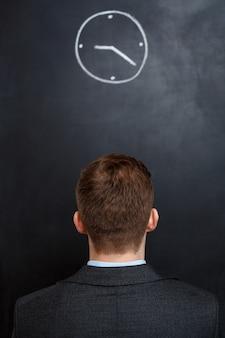 Achtermening van de bedrijfsmens die klok bekijkt