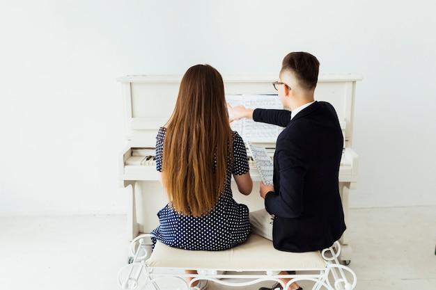 Achtermening van de jonge mens die haar meisjepiano onderwijzen