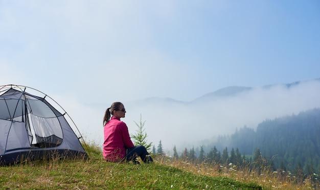Achtermening van de jonge zitting van de backpackervrouw op groen gras van bloeiende vallei bij toeristentent, genietend van mistige bergenmening op heldere de zomerochtend