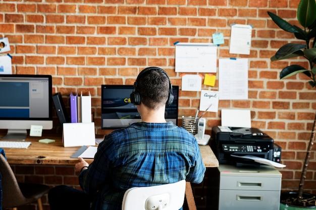 Achtermening van de kaukasische mens die computer met behulp van