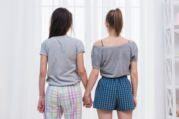 Achtermening van de lesbische handen die van de paarholding venster met wit gordijn bekijken