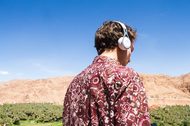 Achtermening van de mens die aan muziek in oase luisteren